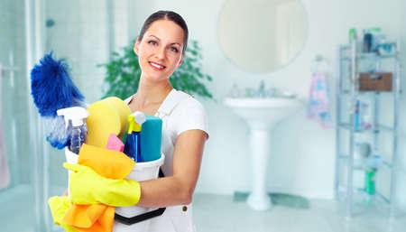 Foto de Young smiling maid. House cleaning service concept. - Imagen libre de derechos