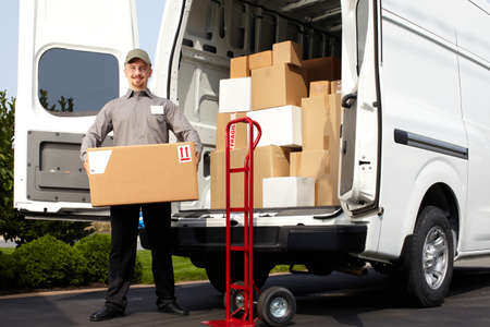 Photo pour Young delivery man with parcel near cargo truck. Shipping service. - image libre de droit