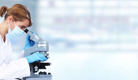 Photo pour Doctor woman with microscope in laboratory. Scientific research. - image libre de droit