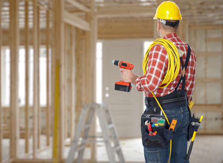 Photo pour Electrician man with drill and wire cable over construction background. - image libre de droit