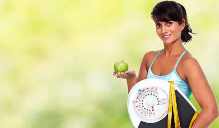 Foto de Young woman with apple and scales. Healthy diet and weight loss. - Imagen libre de derechos