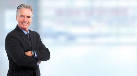 Foto de Smiling mature  businessman over blue background - Imagen libre de derechos