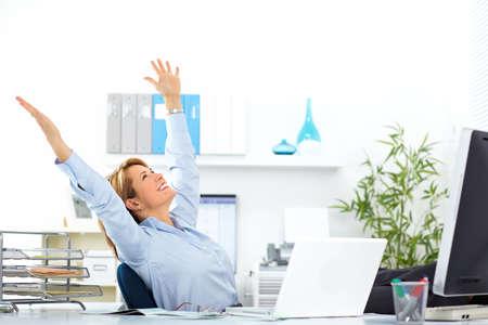 Foto de Beautiful mature business woman relaxing in modern office. - Imagen libre de derechos