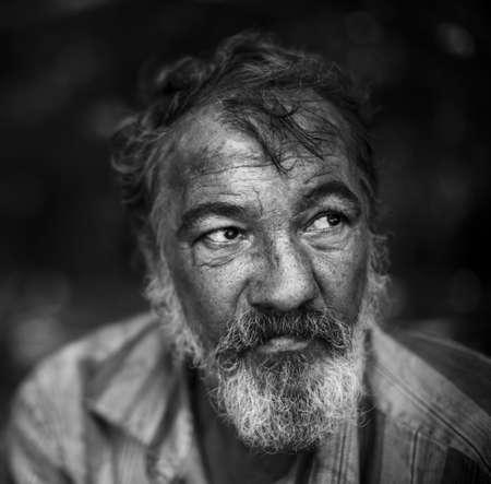 Foto de real homeless man on the dark background, selective focus on eye - Imagen libre de derechos