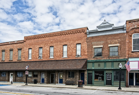 Photo pour A photo of a typical small town main street in the United States of America  Features old brick buildings with specialty shops and restaurants  Decorated with spring flowers and American flags  - image libre de droit