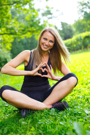 Photo pour Young happy sporty girl showing heart sign with her hands on a meadow in a park - image libre de droit