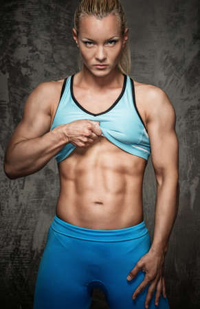 Foto de Attractive bodybuilder girl showing her abdominal muscles  - Imagen libre de derechos