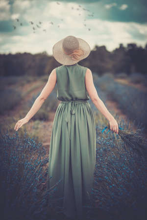 Photo pour Woman in long green dress and hat in a lavender field  - image libre de droit