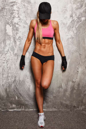 Foto de Sporty woman in pink top with beautiful beautiful body against concrete wall - Imagen libre de derechos