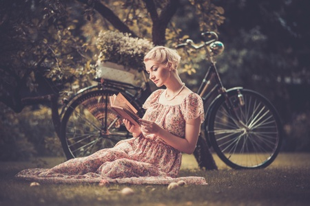 Foto de Blond beautiful retro woman reading book on a meadow - Imagen libre de derechos