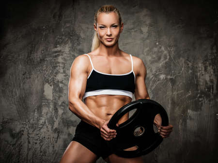 Photo pour Beautiful muscular bodybuilder woman with weights  - image libre de droit