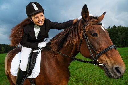 Photo pour Beautiful smiling girl sitting on a horse outdoors  - image libre de droit