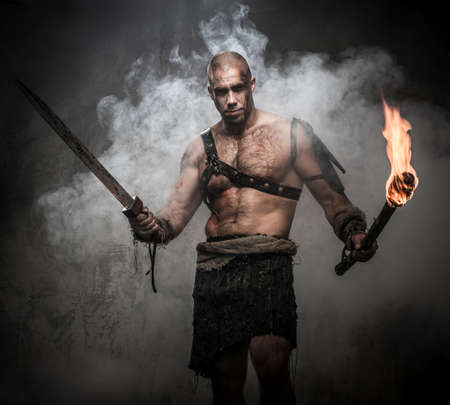Foto de Gladiator standing in a smoke with torch and sword - Imagen libre de derechos