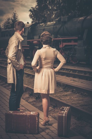 Photo for Beautiful vintage style couple with suitcases on  train station platform - Royalty Free Image