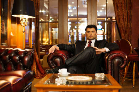 Photo for Confident handsome brunette sitting in luxury interior  - Royalty Free Image