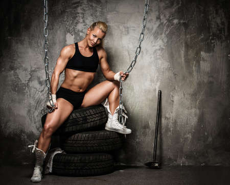Foto de Beautiful muscular bodybuilder woman sitting on tyres and holding chains  - Imagen libre de derechos