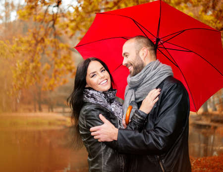 Photo for Happy middle-aged couple with umbrella outdoors on beautiful rainy autumn day   - Royalty Free Image