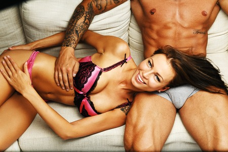 Photo for Young beautiful sexy couple in underwear lying on sofa - Royalty Free Image