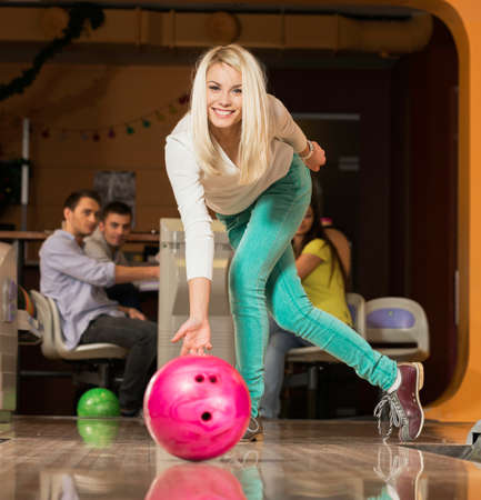 People watching young blond woman throwing bowling ball