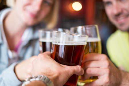Foto de Friends with beer toasting in a pub  - Imagen libre de derechos