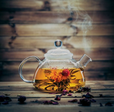 Foto de Glass teapot with blooming tea flower inside against wooden background  - Imagen libre de derechos