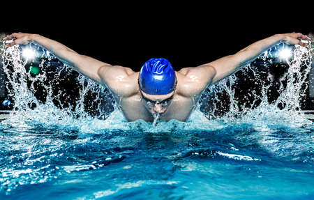 Photo pour Muscular young man in blue cap in swimming pool - image libre de droit