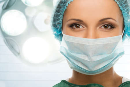 Photo for Young woman doctor in cap and face mask in surgery room interior - Royalty Free Image