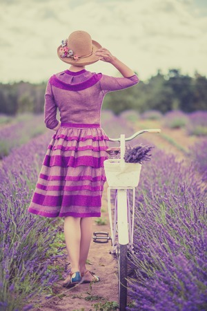 Photo pour Woman in purple dress and hat with retro bicycle in lavender field - image libre de droit