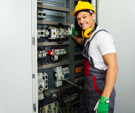 Foto de Cheerful electrician in a safety hat on a factory - Imagen libre de derechos