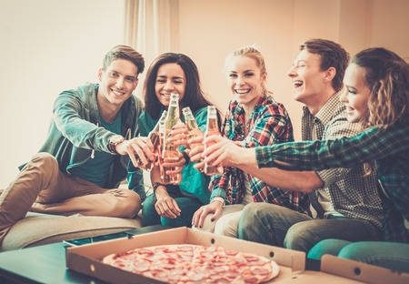 Photo for Group of young multi-ethnic friends with pizza and bottles of drink celebrating in home interior - Royalty Free Image