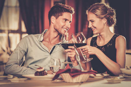 Photo pour Beautiful young couple with glasses of red wine in luxury restaurant - image libre de droit