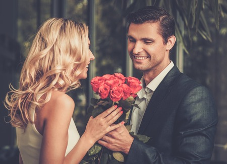 Photo pour Handsome man with bunch of red roses dating his lady - image libre de droit
