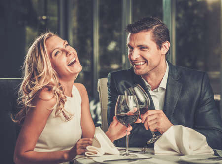 Foto de Cheerful couple in a restaurant with glasses of red wine - Imagen libre de derechos