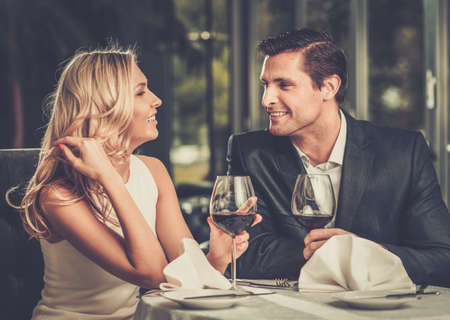 Photo pour Cheerful couple in a restaurant with glasses of red wine - image libre de droit