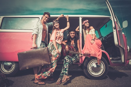 Foto de Multi-ethnic hippie friends with guitar on a road trip - Imagen libre de derechos