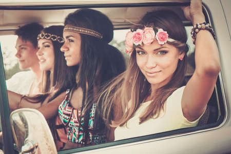 Photo pour Multi-ethnic hippie friends in a minivan on a road trip - image libre de droit