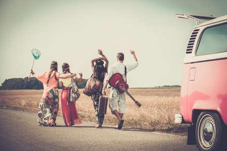 Photo pour Multi-ethnic hippie friends with guitar and luggage  - image libre de droit