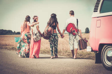 Photo for Multi-ethnic hippie friends with guitar and luggage  - Royalty Free Image