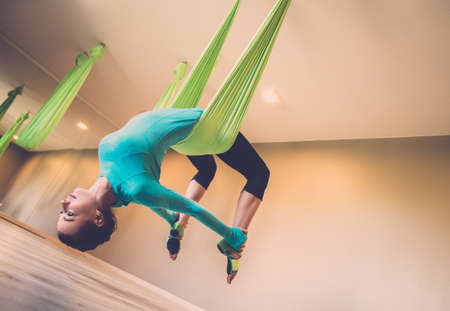 Foto de Young woman performing antigravity yoga exercise  - Imagen libre de derechos