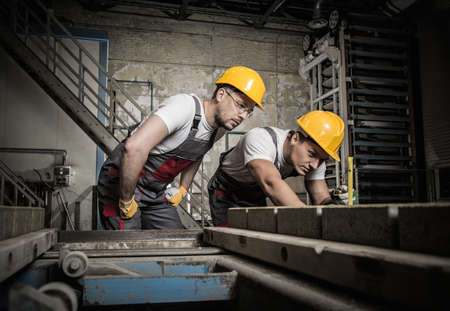 Photo for Worker and foreman in a safety hats performing quality check on a factory   - Royalty Free Image