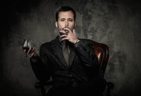 Photo pour Handsome well-dressed with glass of beverage and cigar - image libre de droit