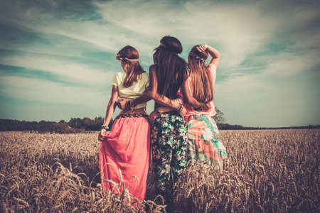 Foto de Multi-ethnic hippie girls  in a wheat field - Imagen libre de derechos