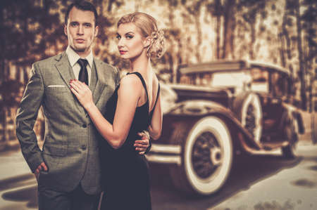 Foto de Beautiful retro couple against vintage car - Imagen libre de derechos