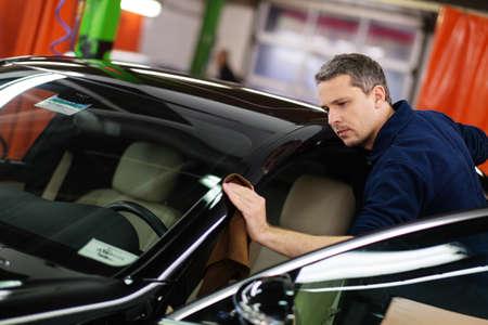 Foto per Man worker polishing car on a car wash - Immagine Royalty Free