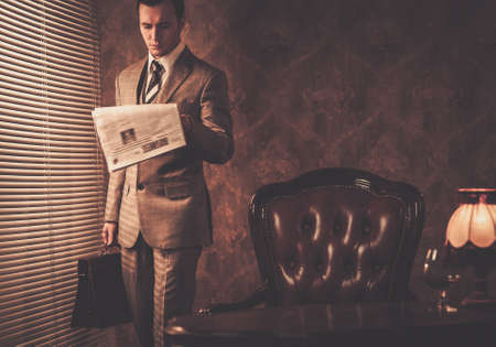 Photo pour Well-dressed businessman reading newspaper - image libre de droit