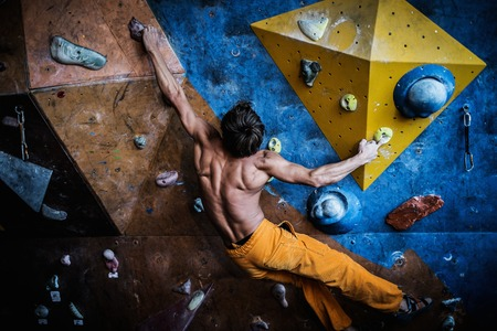 Photo pour Muscular man practicing rock-climbing on a rock wall indoors - image libre de droit