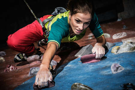 Photo pour Young woman practicing rock-climbing on a rock wall indoors - image libre de droit