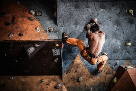 Photo pour Muscular man practicing rock-climbing on a rock wall indoors - image libre de droit
