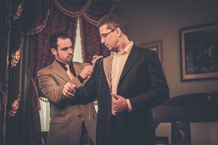 Photo pour Tailor measuring client for custom made suit tailoring - image libre de droit
