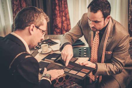 Photo pour Tailor and client choosing cloth and buttons for custom made suit - image libre de droit